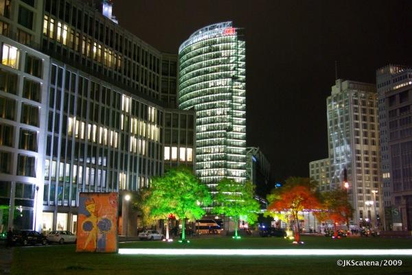 Árvores e fachada do Ritz Carlton iluminadas para o Festival das Luzes, perto da Potsdamer Platz, com o prédio da DB iluminado em destaque